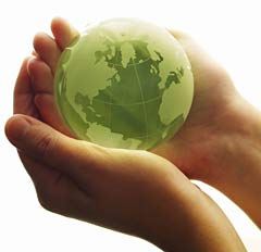 Photo of a pair of hands holding a green globe made of glass.
