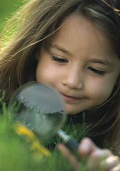 Photo of a young girl examining something in a lawn using a magnifying glass.